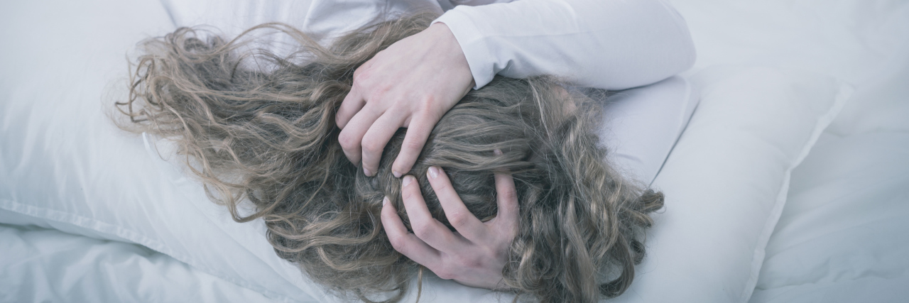 young woman curled up in bed depression anxiety