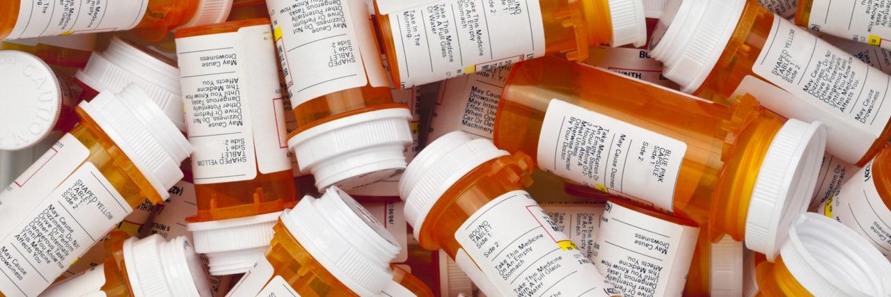 Dozens of prescription medicine bottles in a jumble.