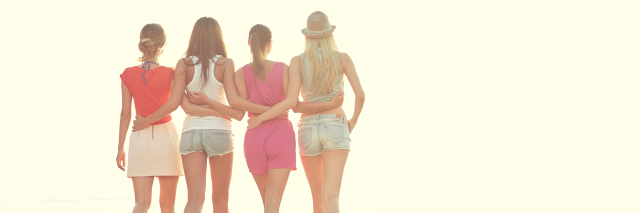friends hugging and walking on the beach