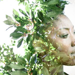 Double exposure portrait of woman combined with photograph of leaves