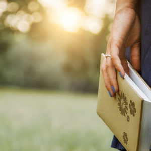 Woman carrying book in hand while walking on grass outdoors
