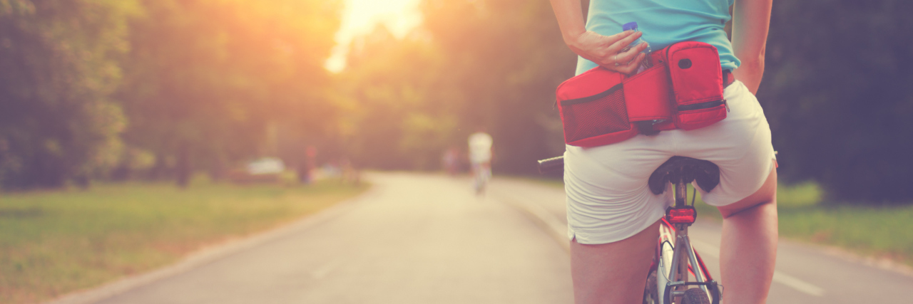 female cyclist on sunlit road stopped for breath with hand on lower back
