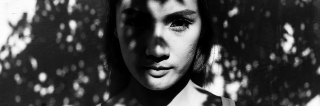 Young woman standing in tree shadows