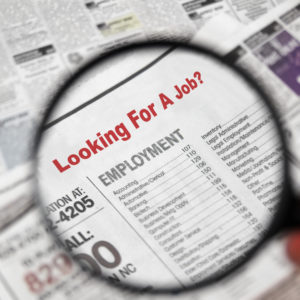 Magnifying glass over Jobs section of newspaper classifieds.