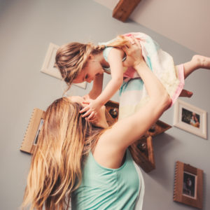 Woman holding her daughter up in the air