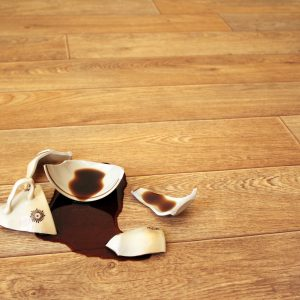 broken coffee mug on wooden floor with spilled coffee