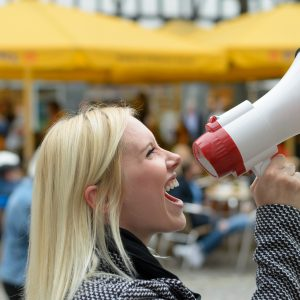 woman yelling into megaphone on the street