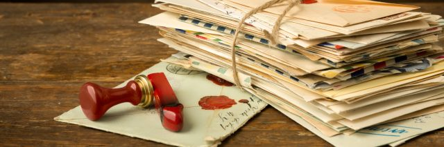 Stack of letters and a wax seal on a wooden surface.