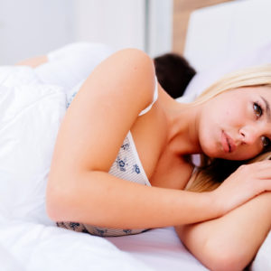 woman in bed upset with man behind her sleeping