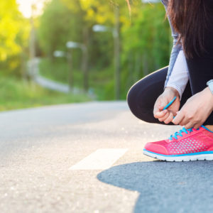 A female runner tying her shoes.