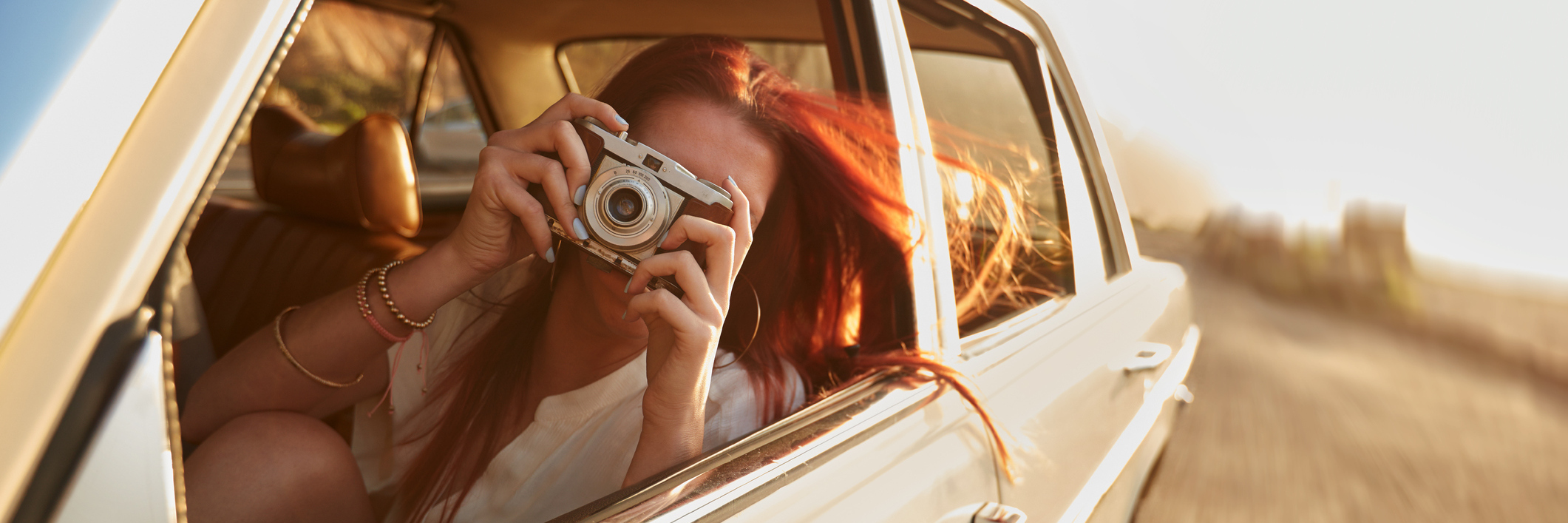 A woman taking a photo from the car.