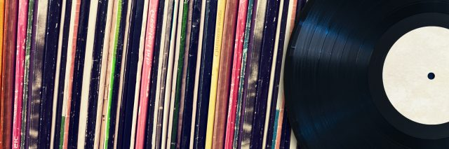 A record in front of record cases on a shelf.