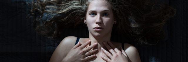 woman lying awake hands on chest afraid upset