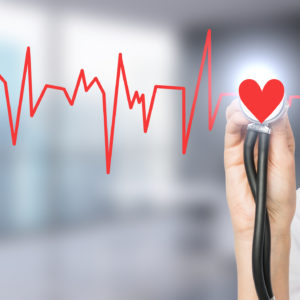 hand listening to a red heartbeat with a stethoscope