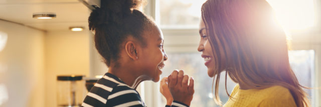 An African American woman and her young daughter smiling at each other.