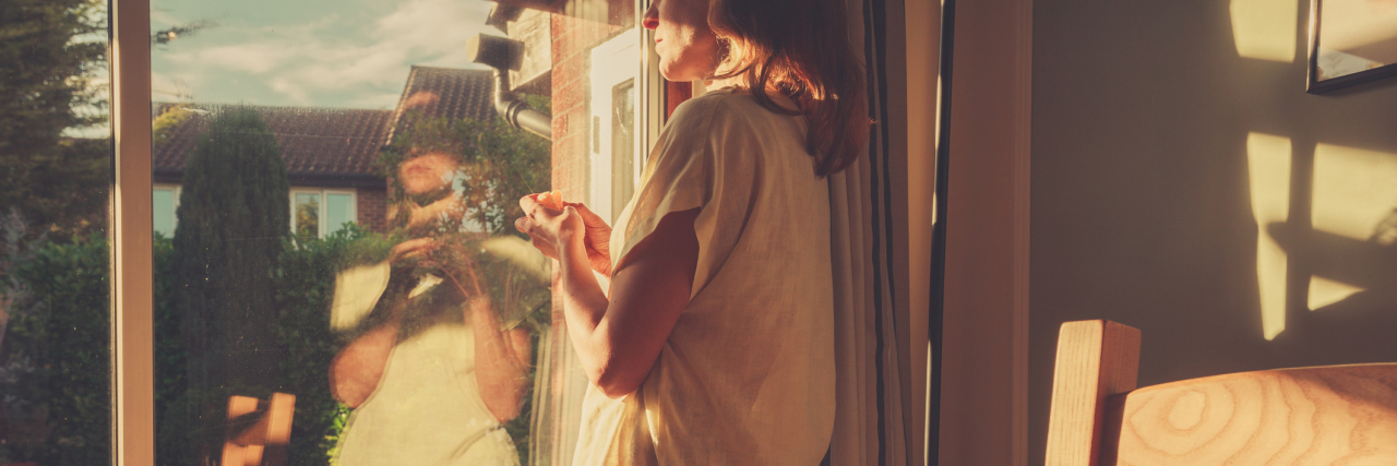 young woman looking out of french doors at sunset