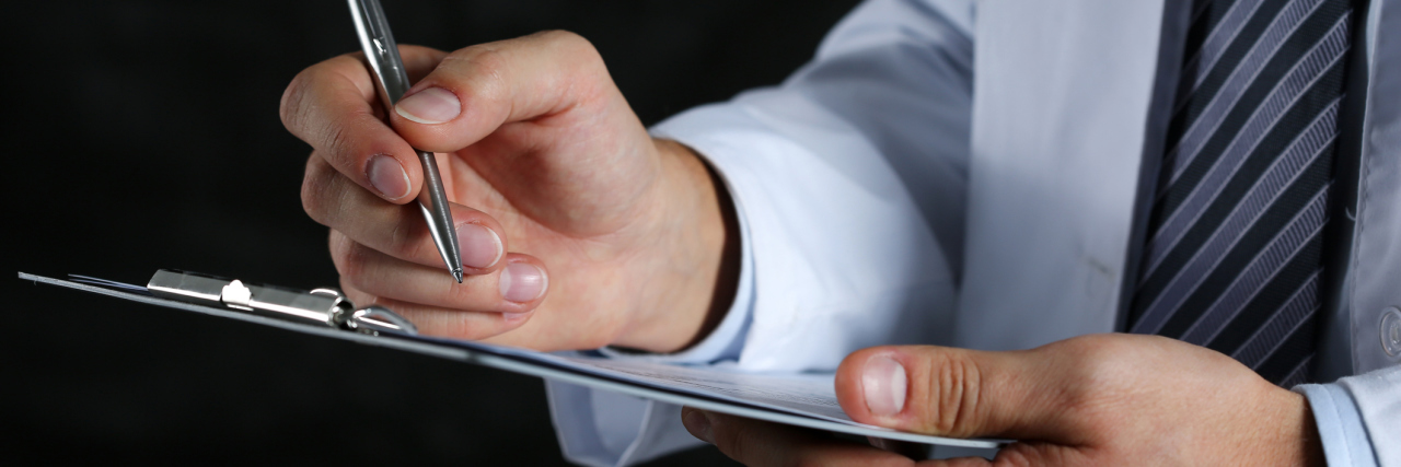 A closeup of a male doctor's hands, writing on a clipboard.