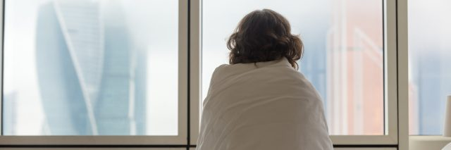 woman sitting on a bed wrapped in a blanket and looking out the window