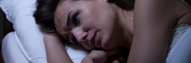 woman lying awake in bed at night