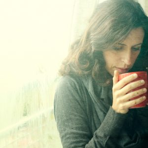 mid 30s woman standing in front of window with red cup of tea or coffee