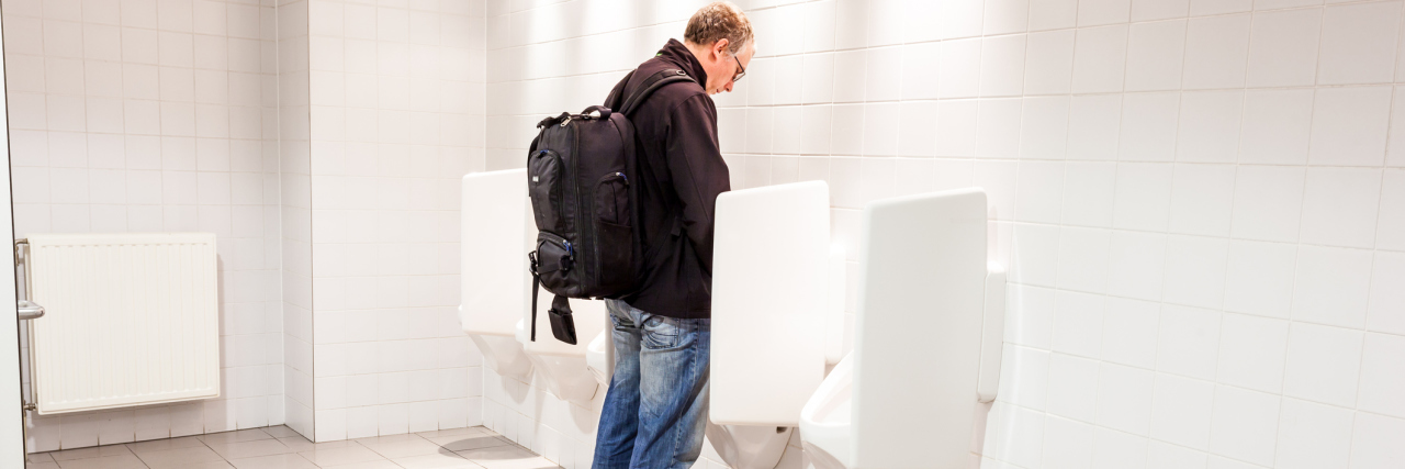 man standing at urinals