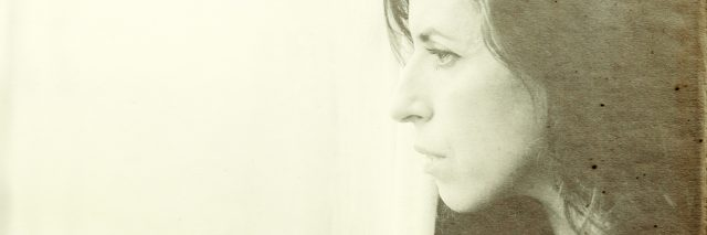 side view of woman looking out of window under sepia filter