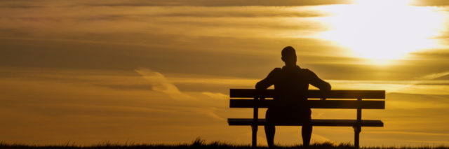 Silhouette man upon a bench looking towards sunset
