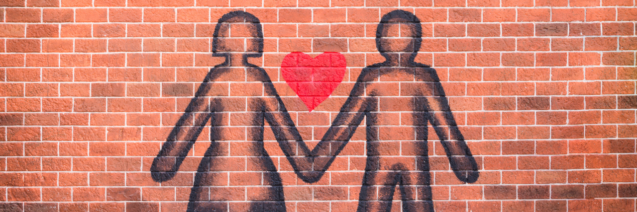 Couple in love sprayed paint on red brick wall