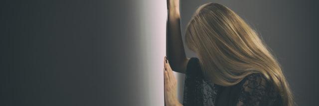 A woman leaning against a wall, hear head looking down.