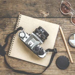 A classic camera on top of a notepad, on a wooden table.