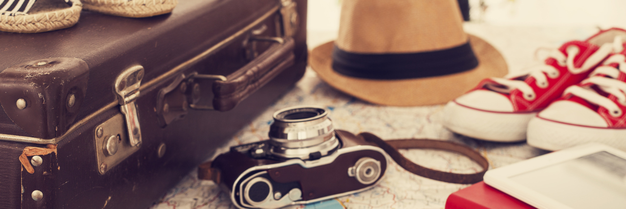 A map in the background with a suitcase, hat, camera, and other travel gear on top.