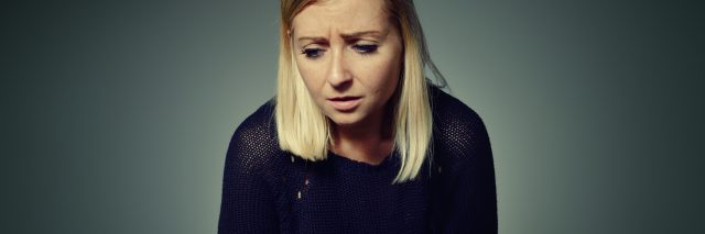 woman looking upset holding stomach in pain or sickness