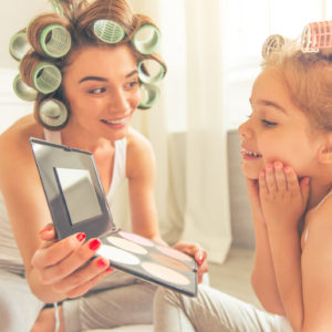 A mom and her young daughter, wearing curlers, looking into a mirror.