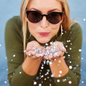 A happy woman wearing sunglasses, blowing glitter.