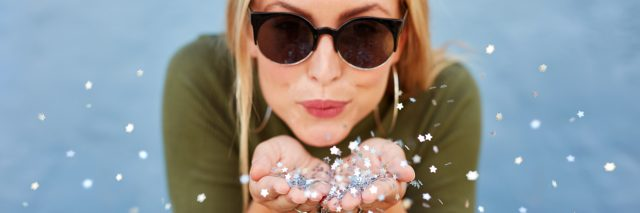 A happy woman wearing sunglasses, blowing glitter.