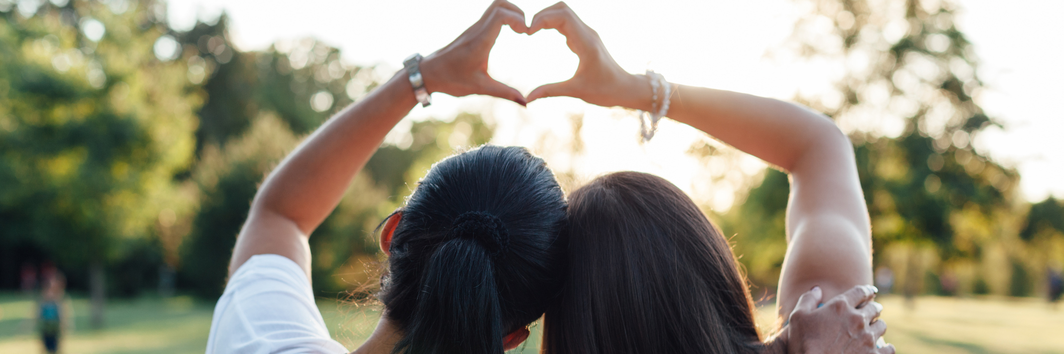 Mom and daughter forming a heart with their hands