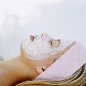 A side profile of a woman laying down, wearing a facial mask.