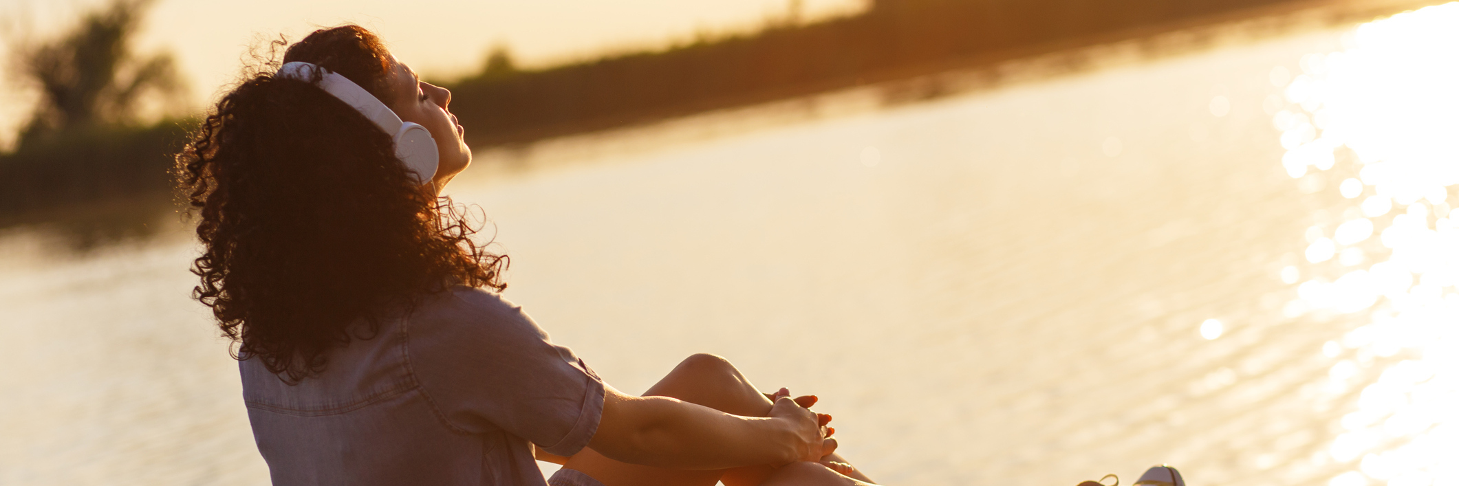 young woman listening to music or meditation on pier at sunset looking relaxed