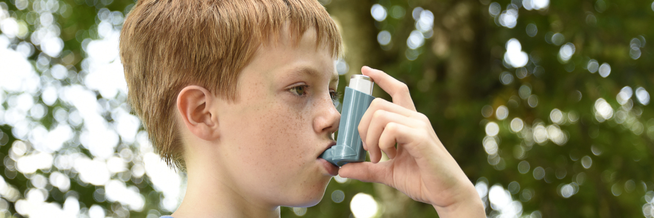A young boy using an inhaler outside.
