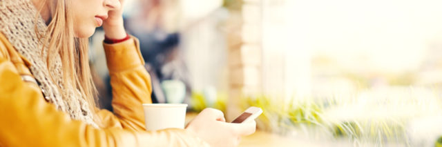 young blonde woman with mobile phone in cafe looking worried