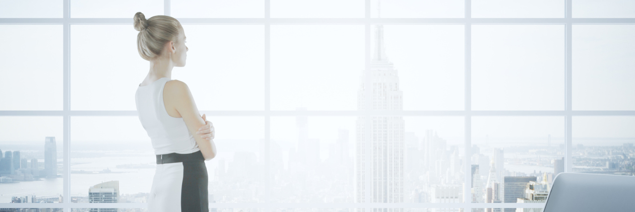 businesswoman looking out her office window