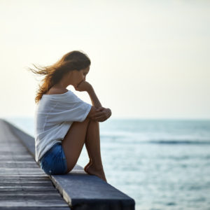 A young woman sitting alone on a pier, looking at a body of water.