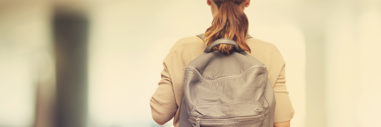Student with backpack walking away from camera.