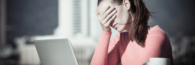 woman stressed by computer covering eyes with hand