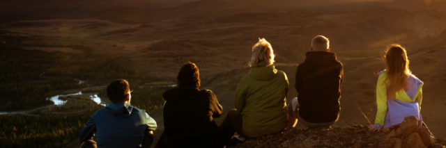 Group of friends sits on the mountain's top on background of mountains and sunset