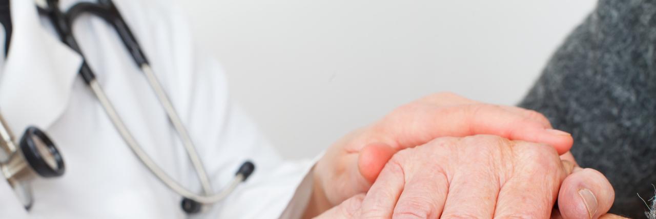 doctor comforting patient's hand