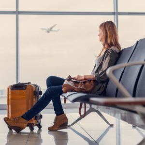 woman waiting in airport with suitcase sitting in front of window