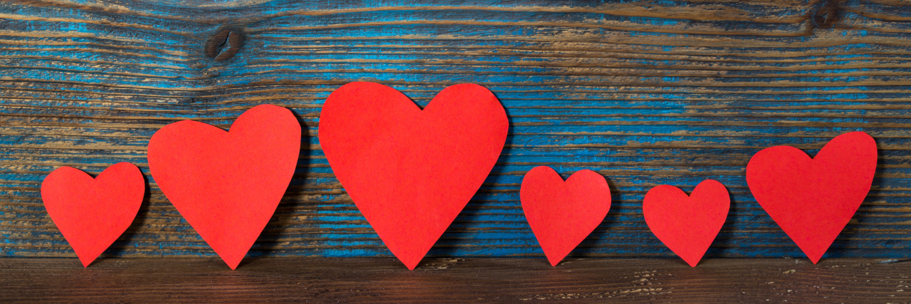 red heart shapes in line on wooden background