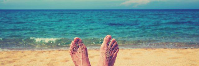 woman's feet relaxing on beach