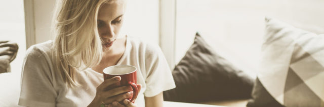 woman resting on couch holding cup of coffee